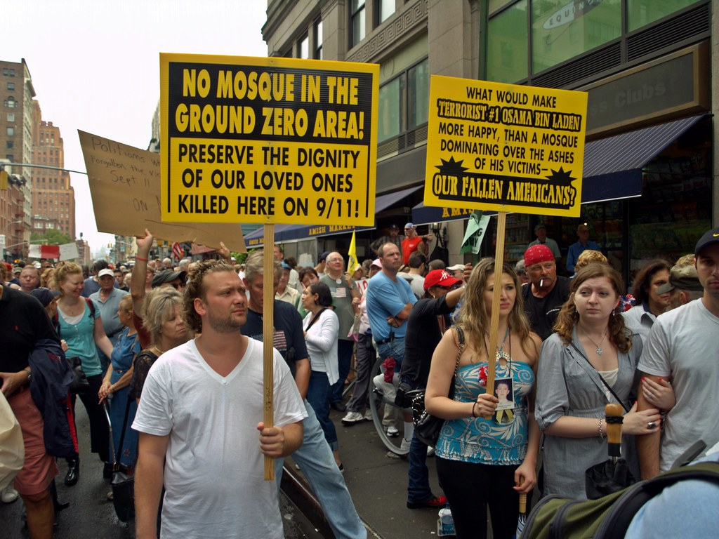 "A white man wearing a white T-shirt holds a sign on the left that states in all capital letters, ""No mosque in the Ground Zero Area! Preserve the dignity of our loved ones killed here on 9/11!"" Nearby, another white woman wearing a necklace with an image of a white man hanging on her chest holds a sign written in all capital letters that states, ""What would make terrorist #1 Osama bin Laden more happy, than a mosque dominating over the ashes of his victims—our fallen Americans?"" Surrounding these two individuals holding signs is a large crowd of white people protesting in the middle of a New York City street."