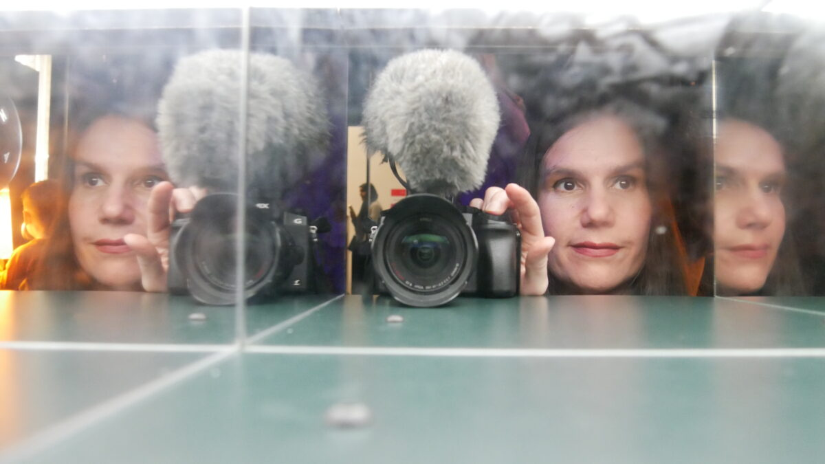 Alexandra can be seen holding a camera with her face reflected on the left and right by mirrors.