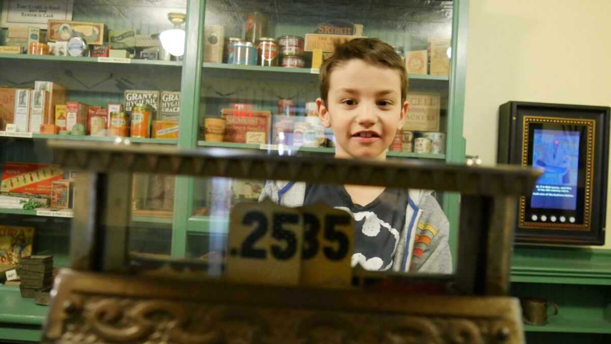 William can be seen behind a vintage cash register standing in front of shelves of canned goods and boxes.