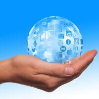 Hand holding a social media globe.