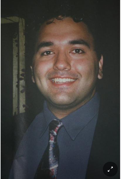 Image of Mohammad Salman Hamdani wearing a blue dress shirt and tie, smiling at the camera.