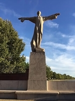 Image of Women's Titanic Memorial statue. Shows a stone statue of a figure standing on a pedestal with outstretched arms.