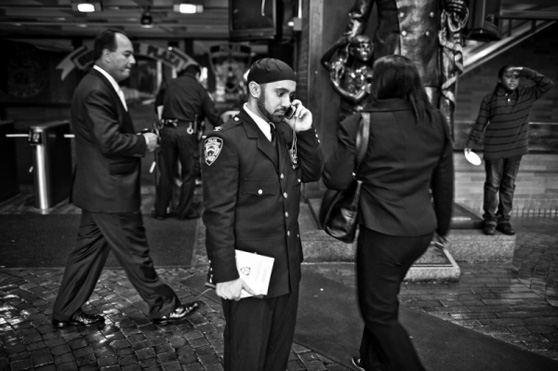 Black and white photo of NYPD Chaplain Khalid Latif. Multiple people are walking around behind him while he stands still in uniform speaking on a cell phone.