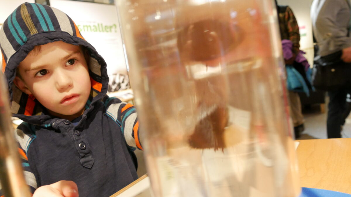 Santiago can be seen wearing hoodie looking at a golden clear glass tube with nano technology inside.