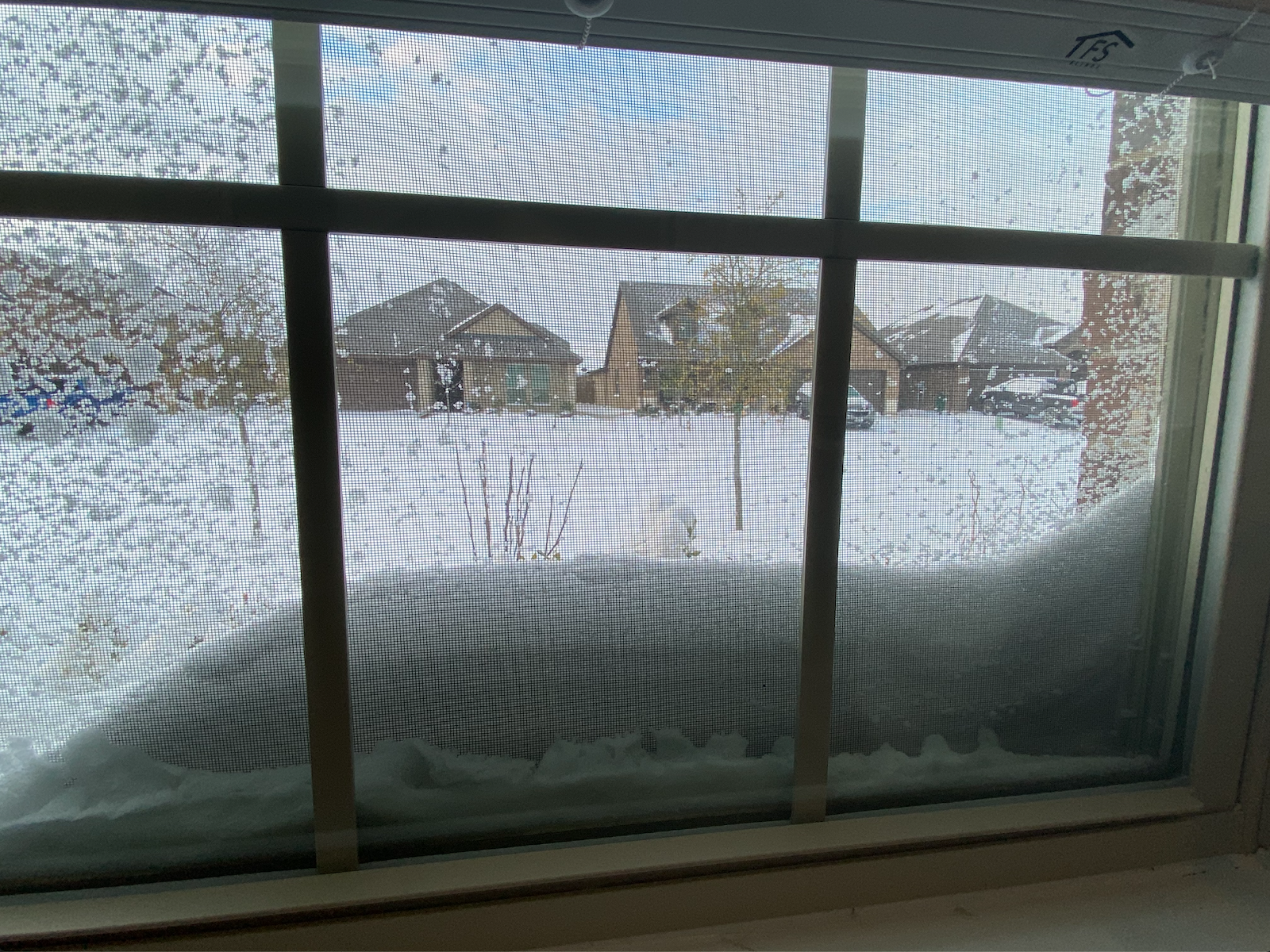 An image of snow piled up against a window in a suburban neighborhood