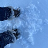 An image of Jo's boots in the snow, taken from up above.