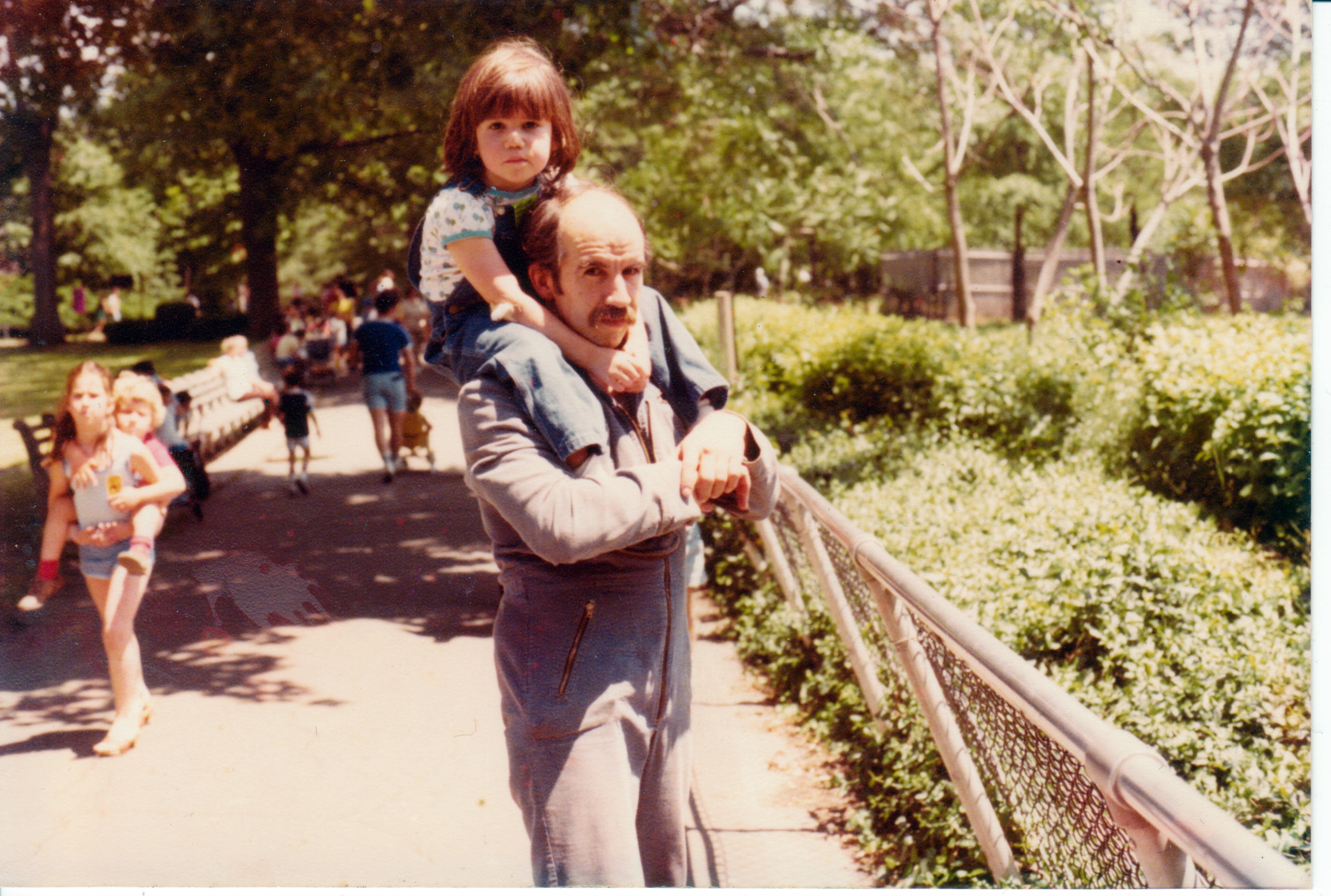 An old photo of a young Alex sitting on her dad's shoulders. They are standing on a bridge in Caracas, surrounded by bushes and the like.