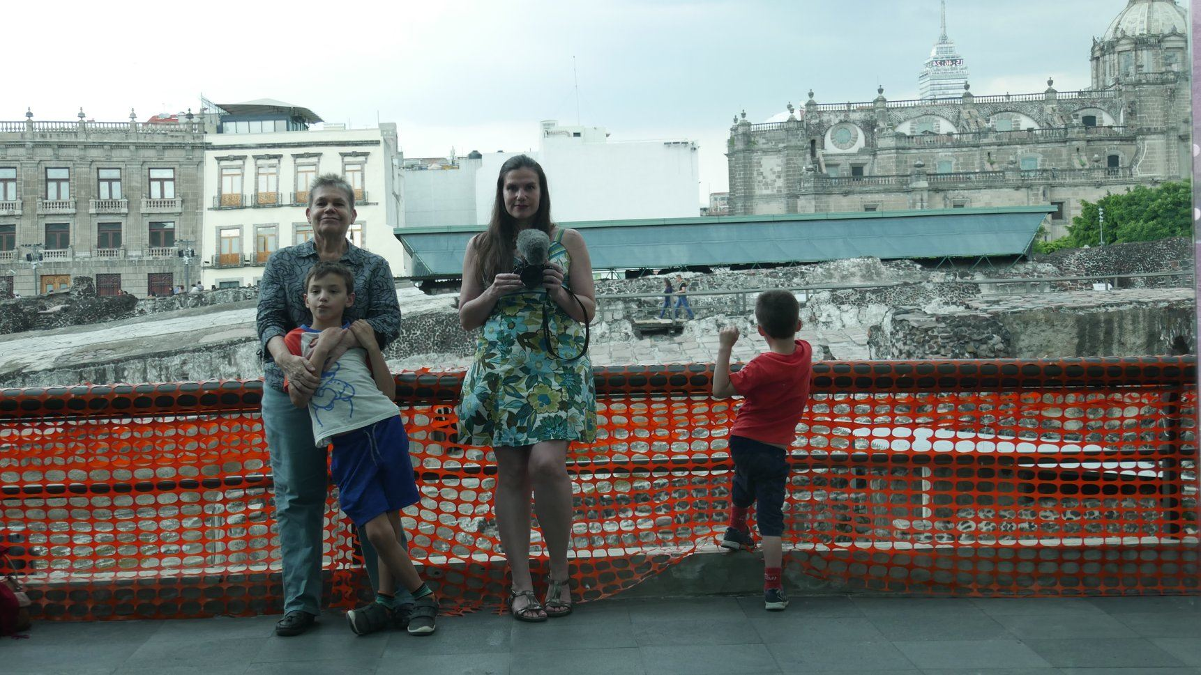 Alex, her two sons and her mother wear summery clothes as they pose for a photo on a bridge in a city.