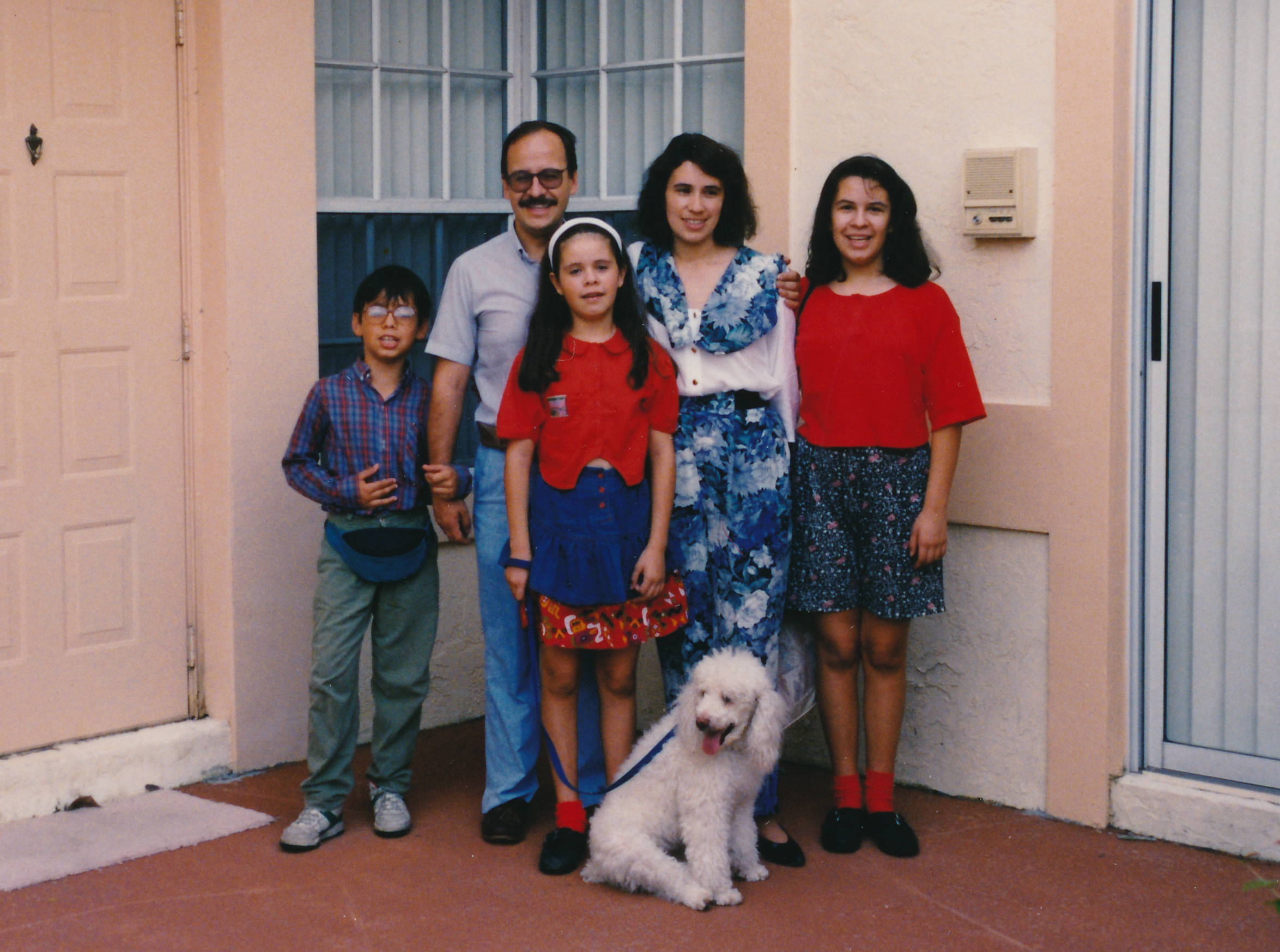 A photo of Ana as a young girl with her two siblings, parents, and a white, fluffy dog. They are all wearing various shades of red, white, and blue, contrasting the pick walls of their home.
