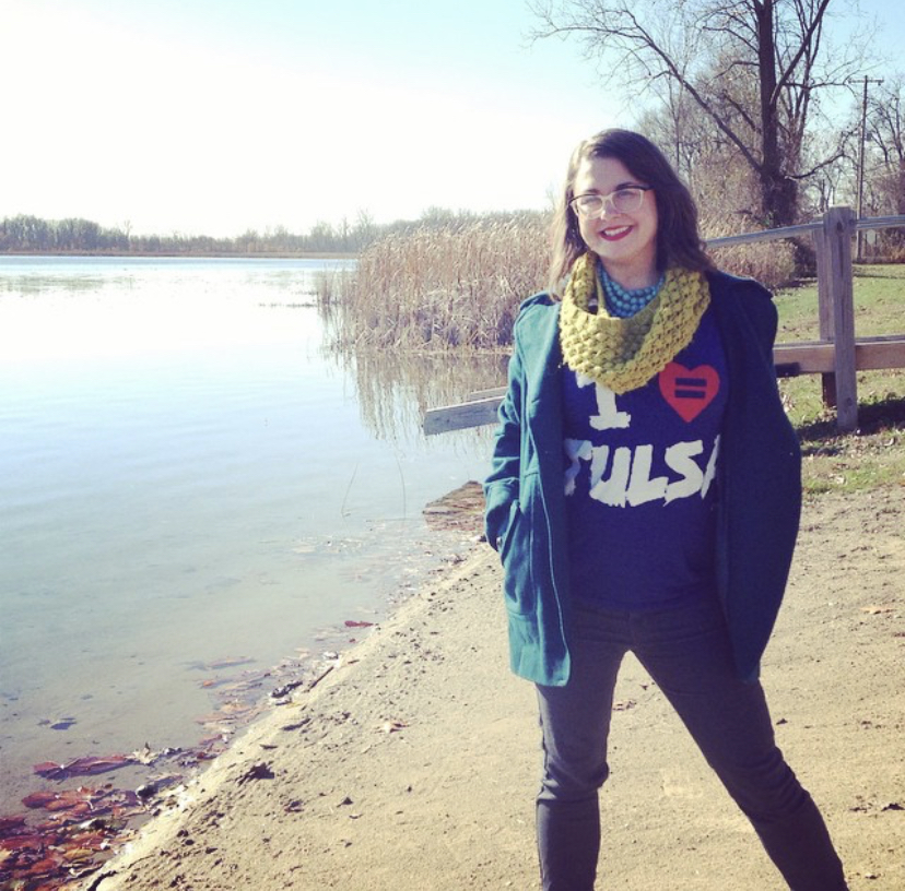 Cat is wearing an I love Tulsa t-shirt, jacket, and yellow scarf while standing next to the shore of a lake on a clear day.