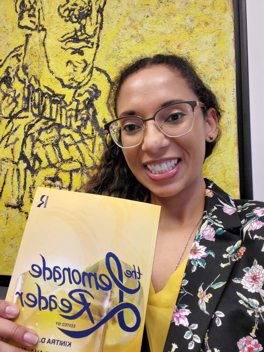 """Lexi is holding up a copy of the yellow-covered """"The Lemonade Reader,"""" smiling at the camera."""
