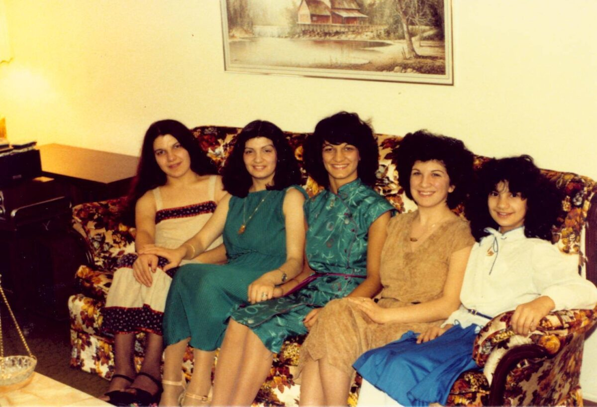 A group of 1980's women sitting in a dated living room with dated hairstyles and fashions.