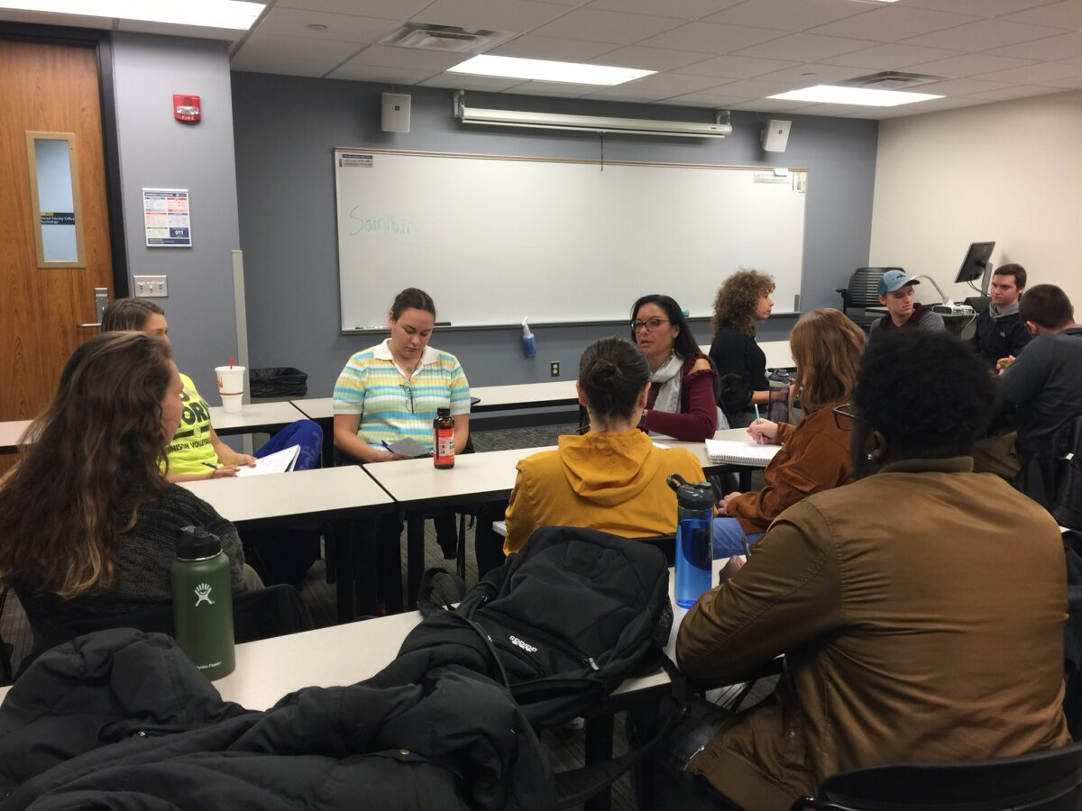 A picture of a standard college classroom with various people in it, having a discussion.