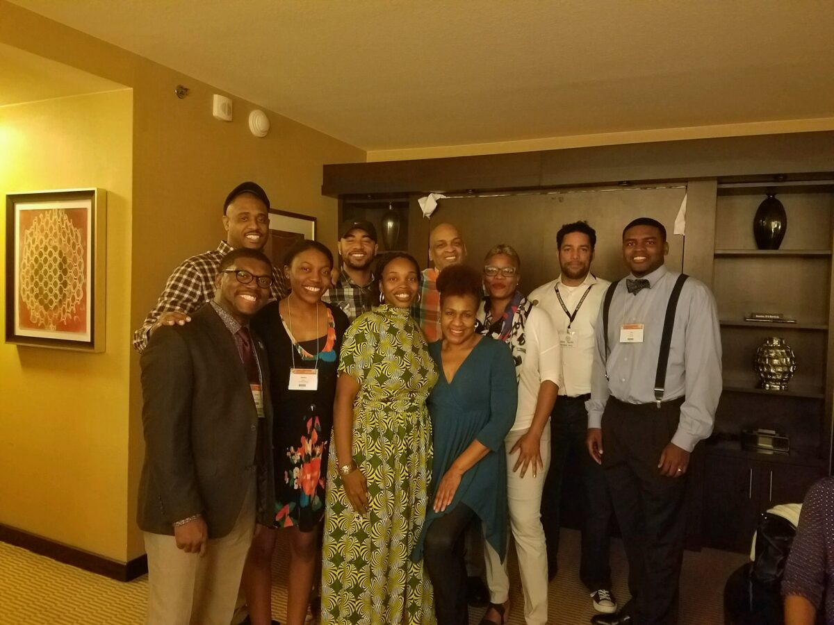 A group of Black scholars stand together in what looks like a hotel room, smiling.