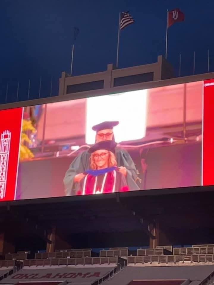 Image of a jumbotron screen at a university stadium where a grad student is getting their hood.