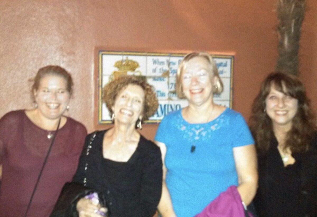 A group of women stand together, smiling in this older, grainy photo.